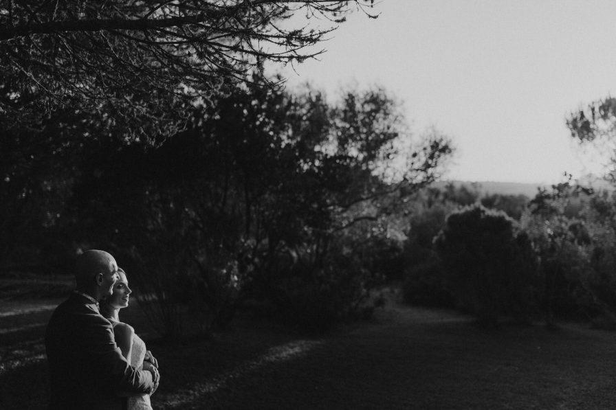 retrato a preto e branco dos noivos abraçados ao por do sol