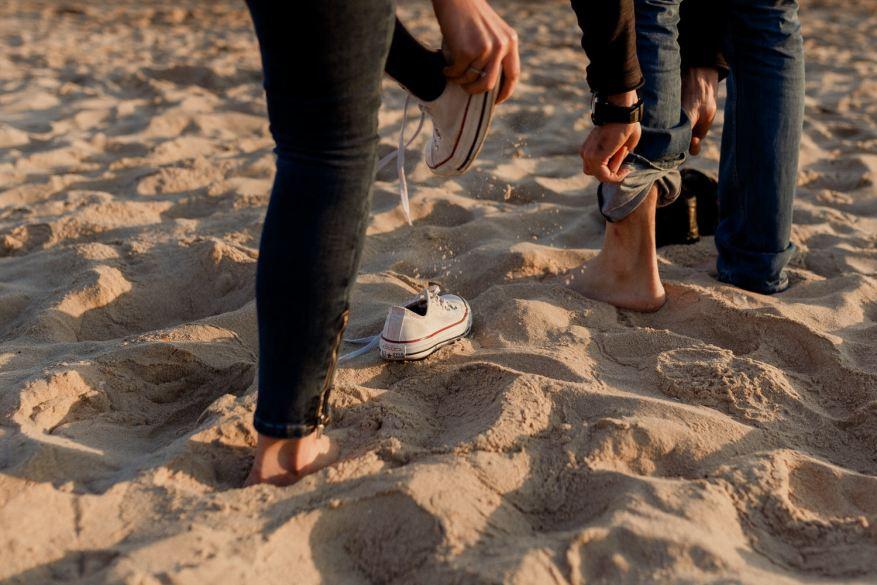 namorados a descalçarem os tenis na areia da praia