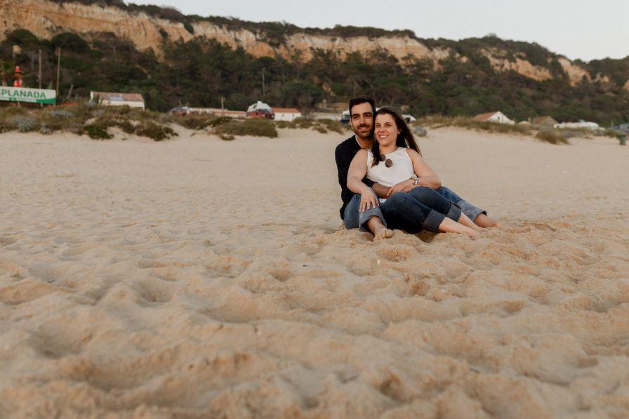 couple in love hugging the in sand of the fonte da telha beach