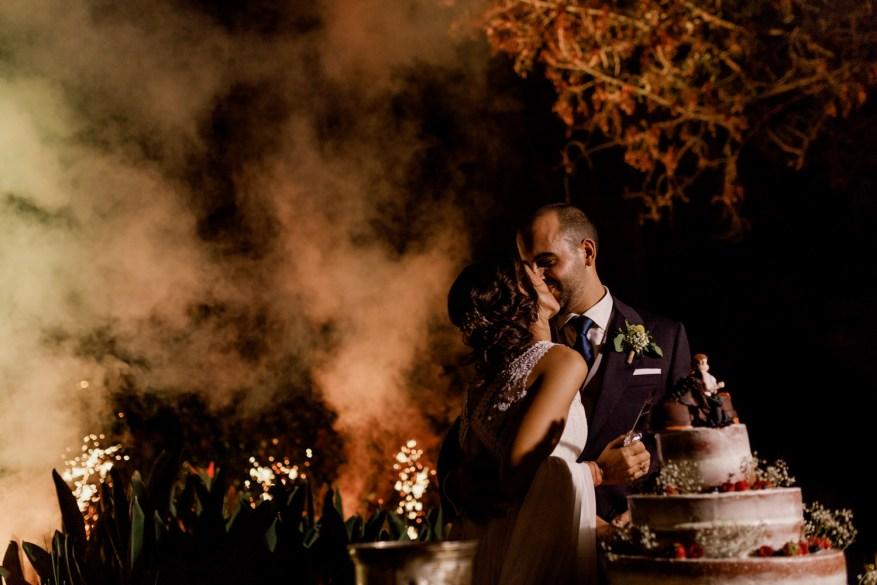 noivos beijam durante o corte do bolo