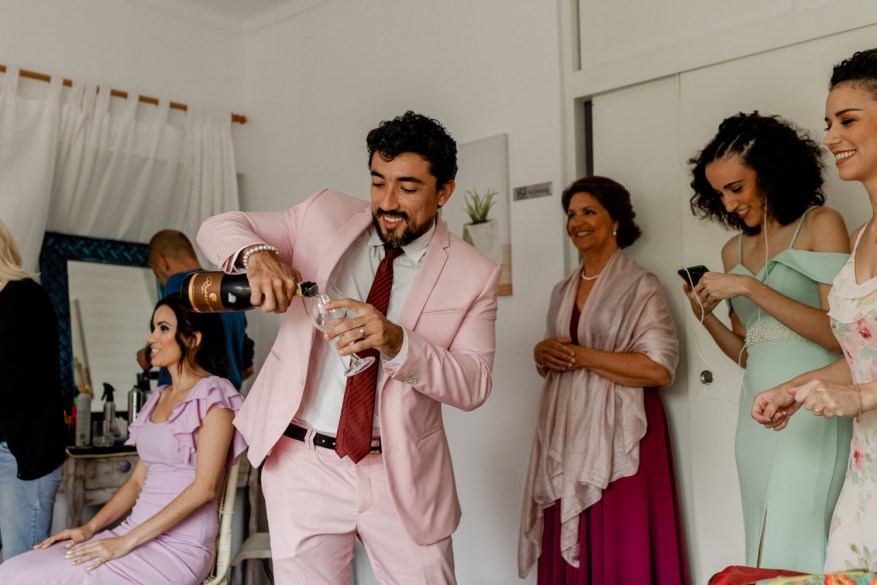 wedding guests open a bottle of champagne