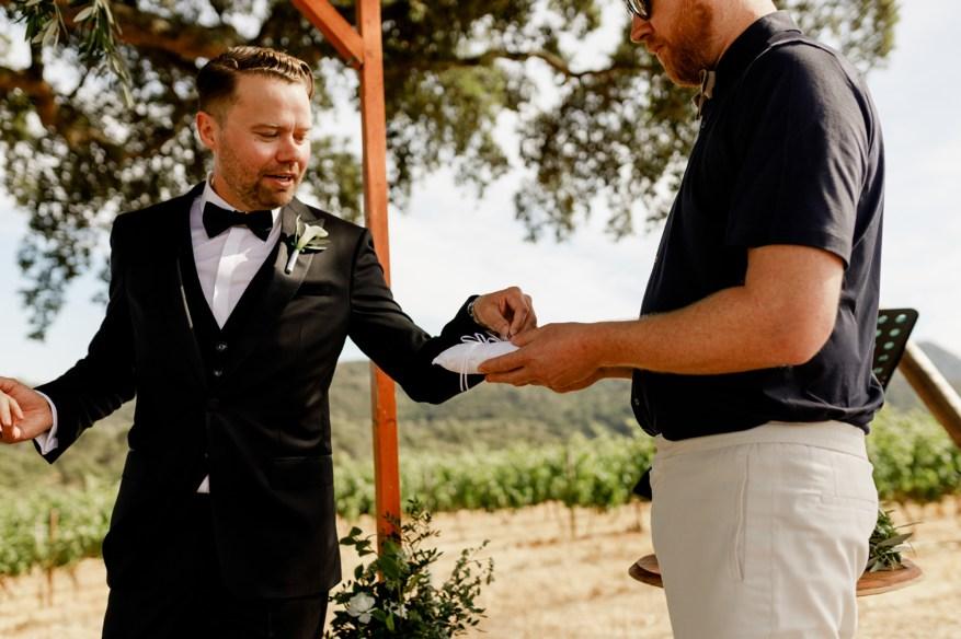 groom takes wedding ring