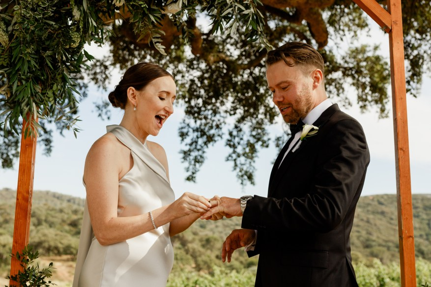 bride puts wedding ring on the groom's hand