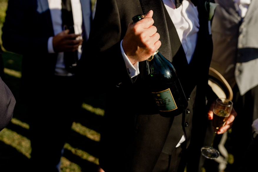 wedding guest shows bottle of champagne