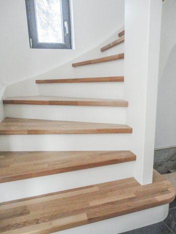 Treppe mit Trittstufen aus Eichenholz und weißen Setzstufen