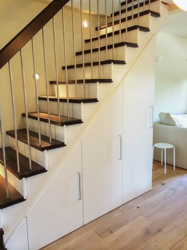 Aufgesattelte Treppe mit gebeizten Trittstufen, Edelstahlgeländer und eingebautem Schranksystem