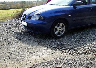 Las piedras sueltas cruzan de lado a lado la carretera que une el municipio de Melide con Toques
