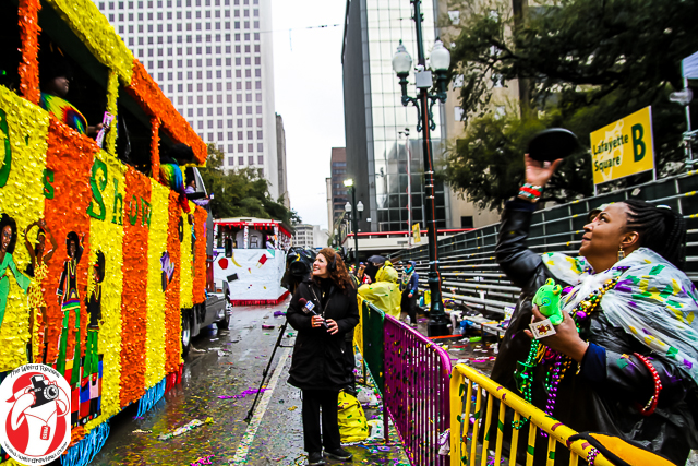 Catching a frisbee after already catching beads and a stuffed animal as this float passed