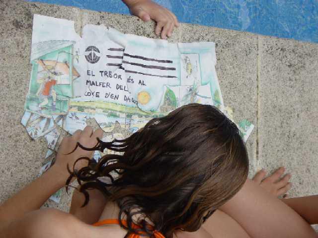Un nen intenta encaixar els trossos dun mapa del tresor