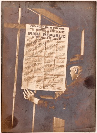 Dr Edmund J. McWeeney inspecting a copy of the Proclamation of the Irish Republic on railings at 84 St. Stephen's Green, Easter Monday, 1916. Image: National Library of Ireland