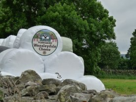 A novel way of advertising cheese: on the side of a hay bale.