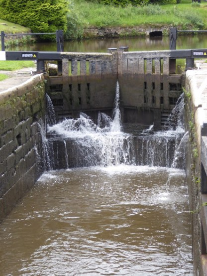 A lock gate slowly letting out water to lower a narrow boat to the stretch below.