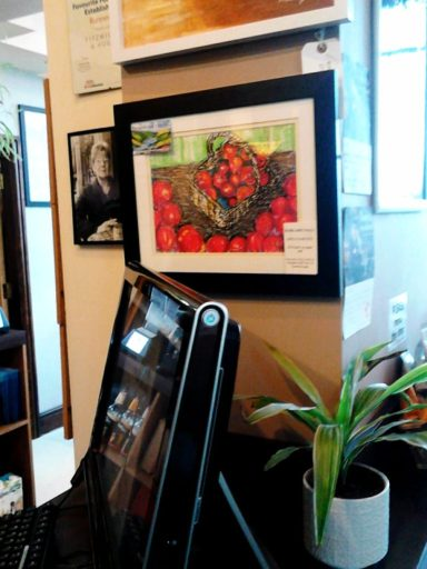 A photo of my oil pastel painting Apples and Fantasy Apples  showing bright red apples in the art cafe exhibition .