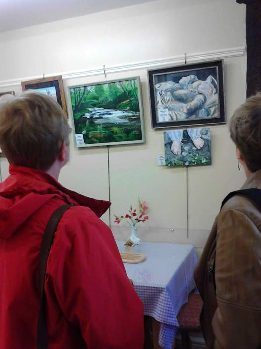 A photo of two visitors, admiring our art exhibition in the museum cafe gallery.