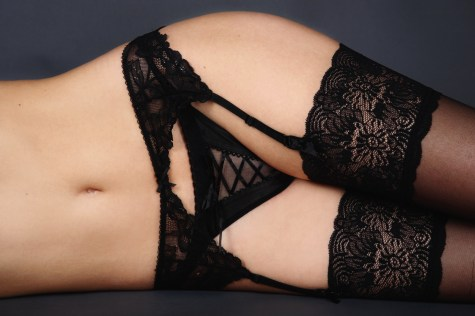 Torso of slim woman in black thong, stockings and garter belt