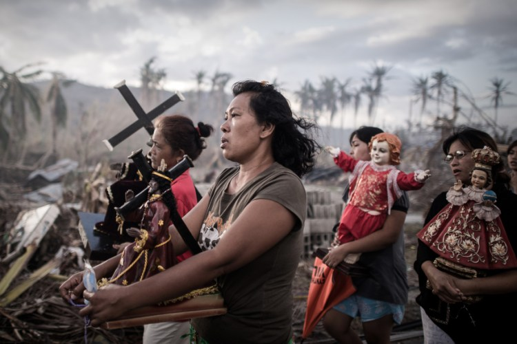Survivors of Super Typhoon Haiyan march during a religious procession in Tolosa on the eastern Philippine island of Leyte on November 18, 2013 over one week after Super Typhoon Haiyan devastated the area.  The United Nations estimates that 13 million people were affected by Super Typhoon Haiyan with around 1.9 million losing their homes.     AFP PHOTO / Philippe Lopez / AFP / PHILIPPE LOPEZ
