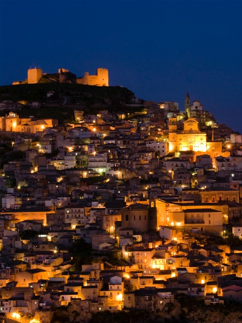 View by night of dwellings and the church of Santa Margherita in the city of Agira in Sicily during celebrations with fireworks