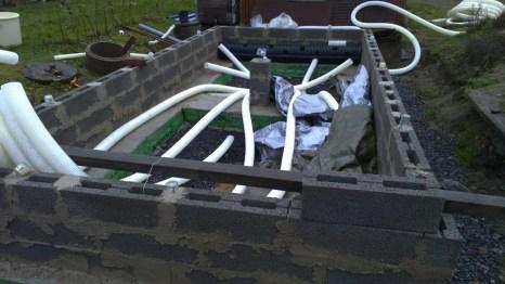 Drei Reihen Betonsteine gemauert und die ersten Luftröhren eingepasst