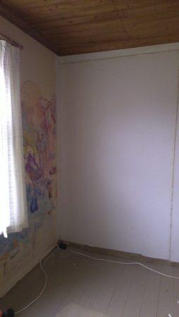 Der neue Spannkarton über der Blockhauswand, neben dem Fenster ist die Wand mit einer isolierenden Platte bedeckt.