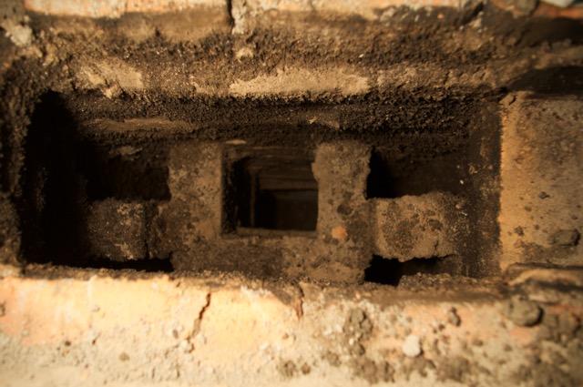 Blick von oben, unter dem mittleren Kanal befindet sich das Feuer, der Rauch stößt an die Decke und geht dann durch die beiden seitlichen Kanäle nach unten, von wo er auf der Hinterseite des Ofens in den Schornstein abzieht