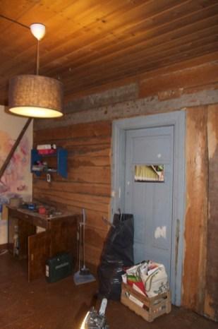 Die Wand zum Wohnzimmer, die oberen zwei Bohlen sind grau, weil sie in einem vorigen Gebäude an der Außenwand gewesen sein müssen, welche mit Lehm verputzt war.