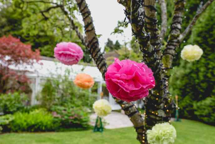 Paper pom poms in hot pink, yellow and orange hang from a tree outside the venue