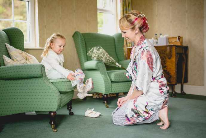 Hatty's daughter plays dress up in her mum's bridal shoes while Hatty looks on and smiles