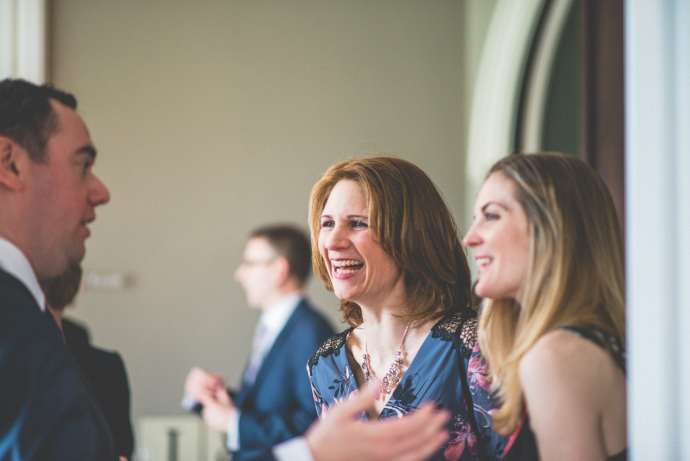 A female guest in a navy blue floral dress laughs at a story being told as the guests mingle after the ceremony