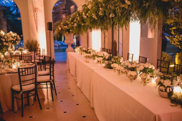 The top table is adorned with an arch of foliage and white flowers, and many bowl vases of white roses