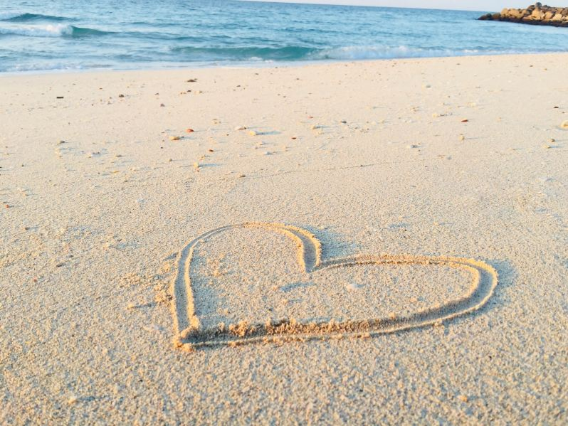 heart drawn on sand during daytime