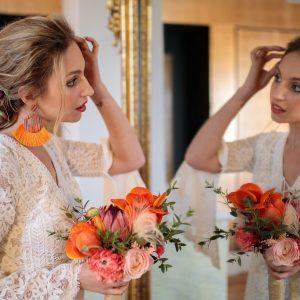mariée et bouquet de mariée orangé, coiffure de mariée, chignon mariage, boucles d'oreilles oranges, mariée devant miroir, maquillage mariage, coiffeuse à domicile, coiffeuse haut de gamme