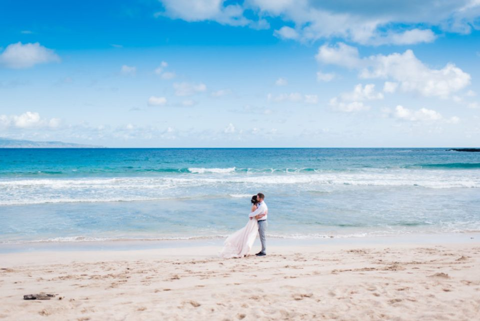 couple standing along the ocean in Kapalua embracing before their maui wedding ceremony