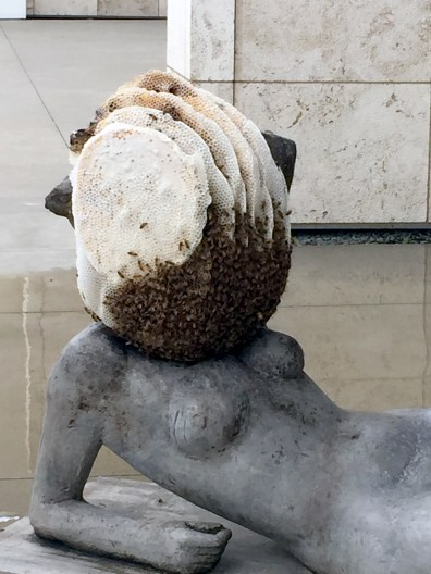 An active beehive on top of nude female statue.