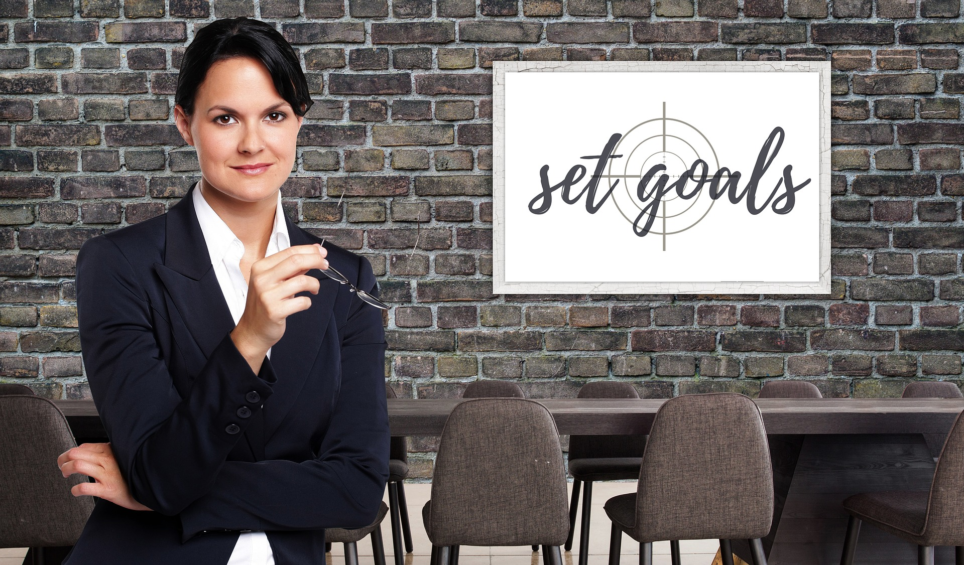 photo of a businesswoman in front of a set goals sign