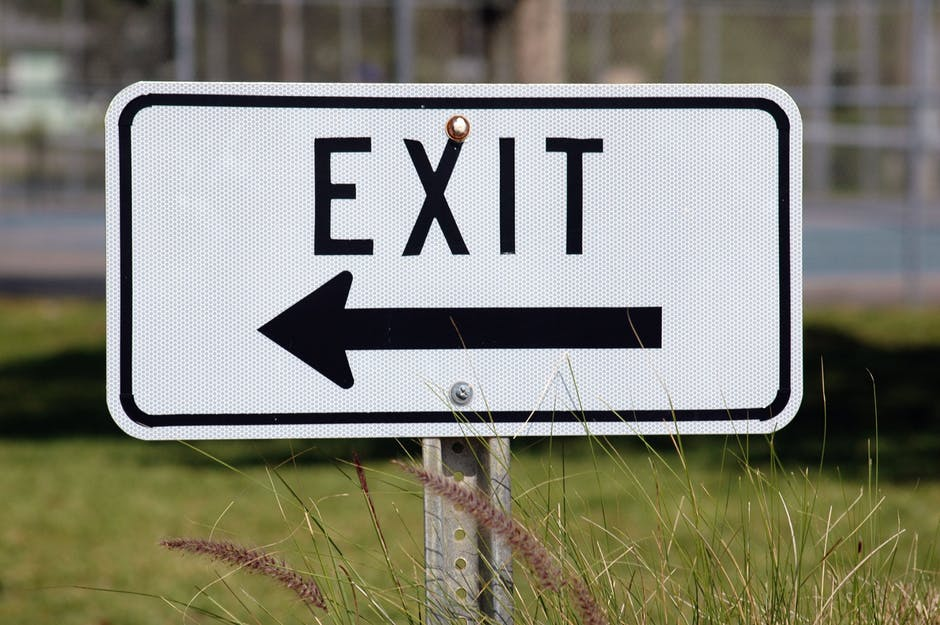 white exit sign with a left pointing arrow as featured int eh article 5 tips to prepare for getting fired on mariedeveaux.com career and life coach.