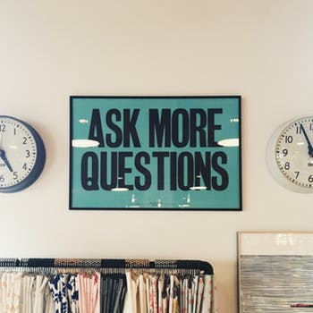 """ask more questions"" poster featured in an office setting between two international clocks and a very full file cabinet. Featured on article about EQ and the One questions every manager should ask on mariedeveaux.com career coach"