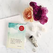 "Image of Marie Kondo's book the Life changing magic of tidying up displayed near a vase of vibrant flowers as featured in article ""Just say no"" on mariedeveaux.com career coach"