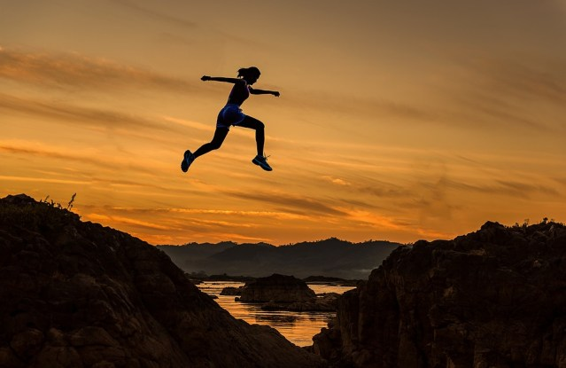 """Image of woman leaping a chasm with a sunset backdrop as featured on article on mariedeveaux.com career counseling website """"why job hopping works"""" about leap frogging in your career"""