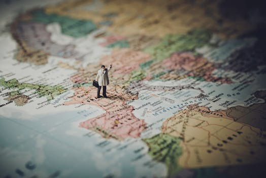 Image of a small man positioned on a world map illustrating the need for a coach or guide on marie deveaux career coaching website
