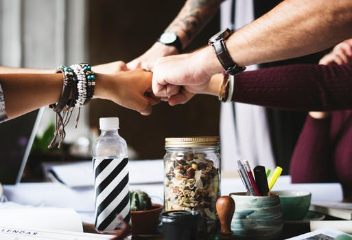 image of 5 hands coming together as a team as featured on marie deveaux business coach website with information about building a board of directors or a squad for the entrepreneur business to go farther and faster.