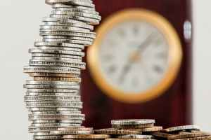 """Image on Marie Deveaux career coach site of stacks of silber and godl coins in foreground and clock inthe back groudn to illustrate how to turn your passions into a viable business """"coins"""""""