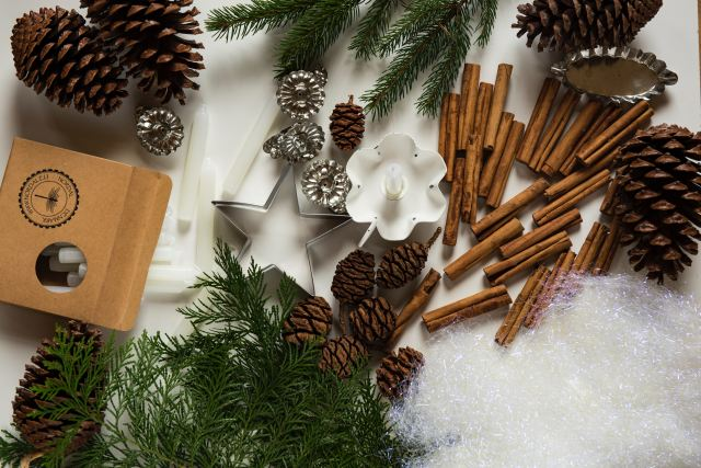 pine cones, cinnamon and evergreen on a table in preparation for December as Marie Deveaux career coach helps busy moms keep the December drama free