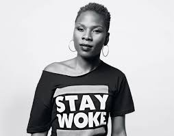 "Luvvie Ahayi pictured in black and white in a ""stay work"" t shirt as Marie Deveaux career coach speaks about the power of community for Black women in America"