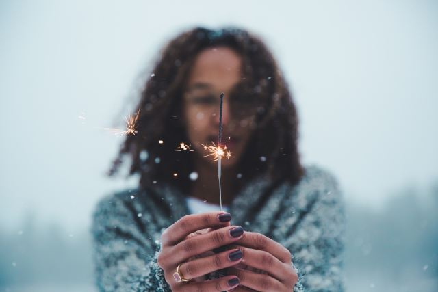 Black woman out of focus holds a sparkler in focus as Marie Deveaux explains the power of meditation.