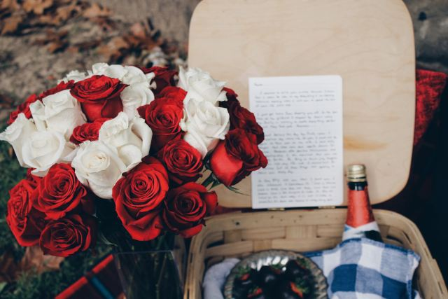 Marie Deveaux career coach speaks on the need for self love on Valentine's Day and displays an image of roses and a picnic basket, complete with wine and a love letter to illustrate how love can come in many forms