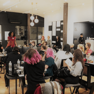 Marie Deveaux, career coach stands and inspires a group of seated women at a networking event for design professionals.