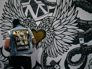 "Marie Deveaux career coach discusses mindset shift and how to break free from the work for money mindset with photograph of man in a jean vest that reads ""The future will be different"" on the back as he paints a black and white mural of a flying, feathered golden heart."