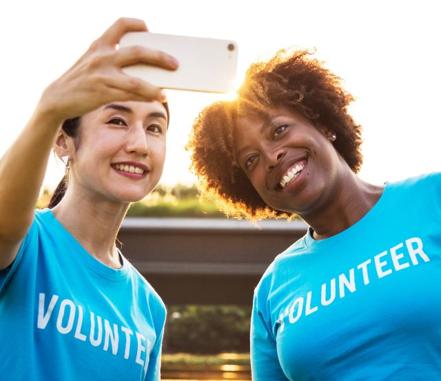 "A black woman and an Asian woman wearing blue shirts with the word ""volunteer"" across their front smile and pose for a selfie together in the setting sun as Marie Devaeux hails tha value of giving of your time in order to receive more opportunities."