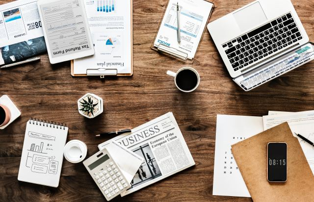 Marie Deveaux career coach discusses how to break free of the work for money mindset. Photograph displays a cluttered wooden table with the business section of a newspaper, paperwork, coffee and a laptop.