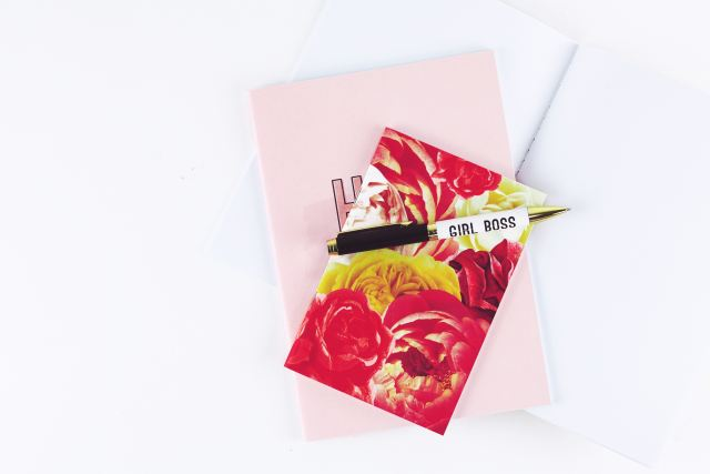 """Picture of a red coloreful notbeook atop a pink book and nea r a pen that reads """"girl boss"""""""